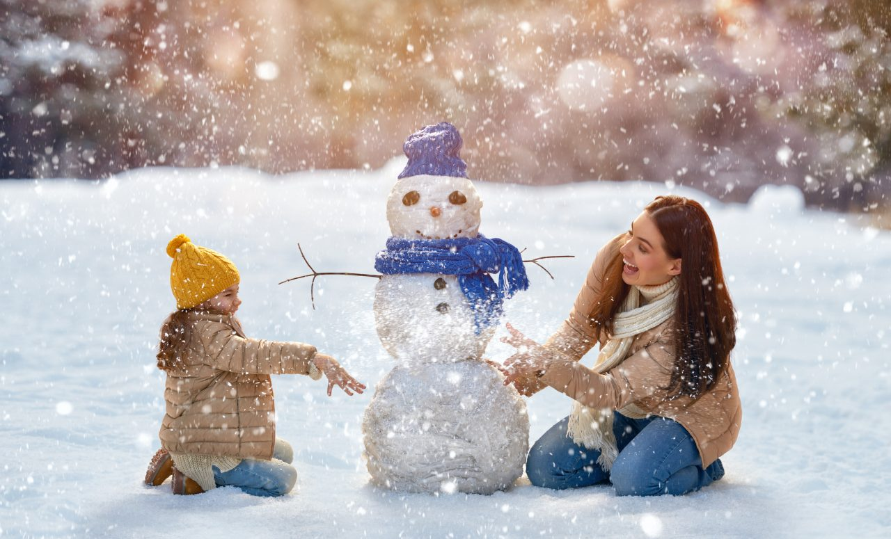 womon and child building a snowman