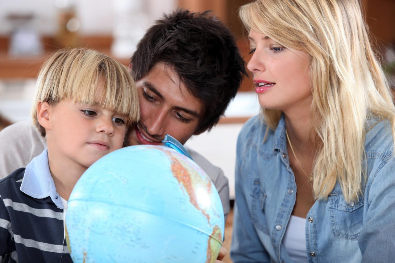 family and child looking at a globe together