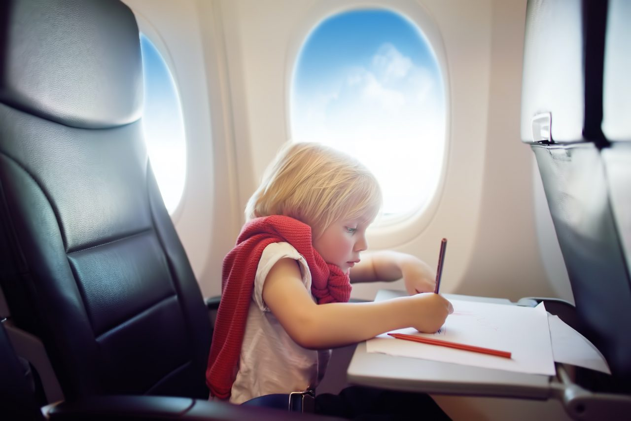 Charming kid traveling by an airplane