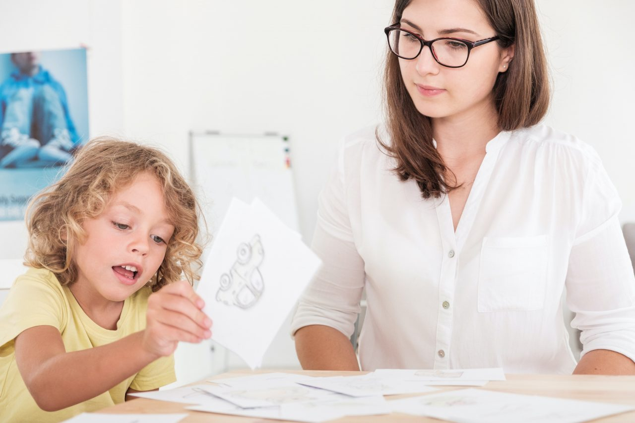 A professional child education therapist using props during a meeting with a kid with problems.