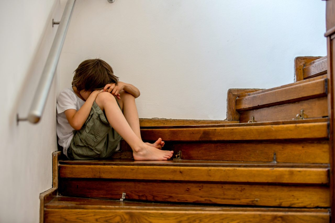 Sad child, sitting on a staircase