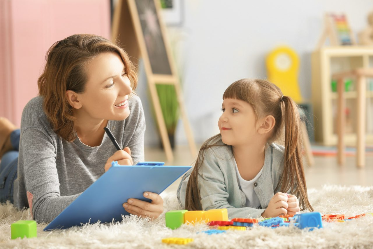 Female psychologist with cute little girl