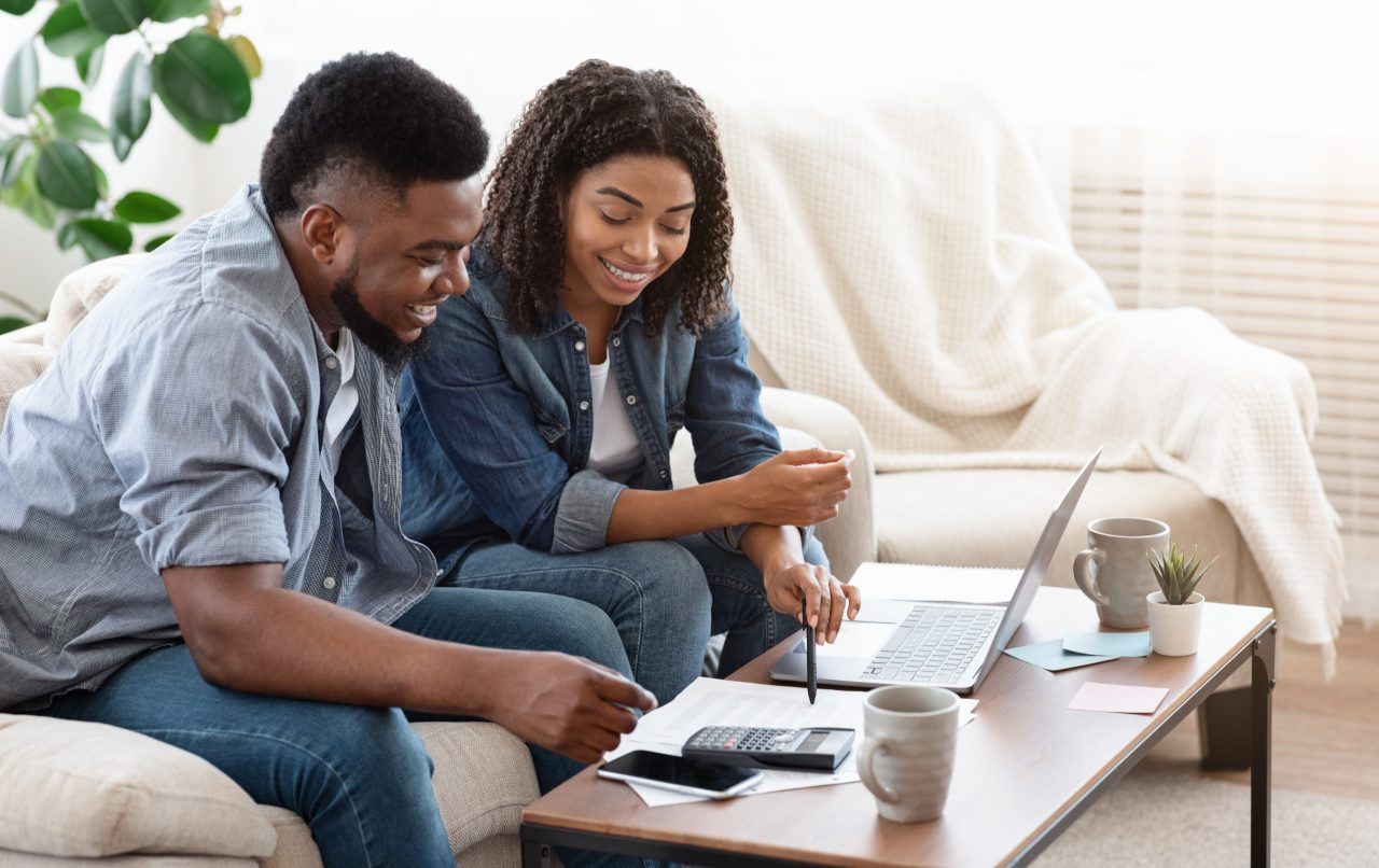 Smiling couple sits in front of a table with a computer, calculator, and papers discussing finances.