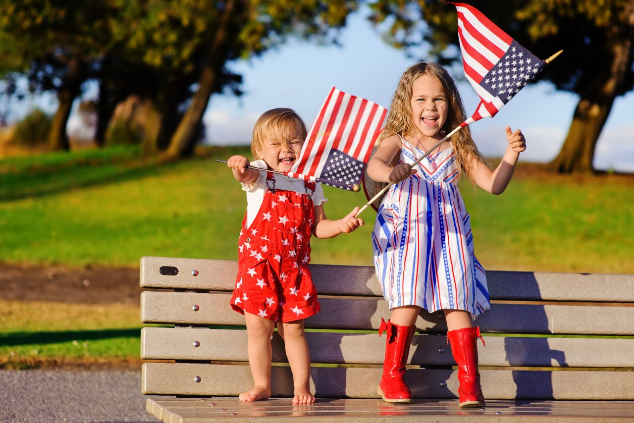 Two little children that look like siblings stand together on a park bench in patriotic red, white, and blue outfits smiling and waving American flags.