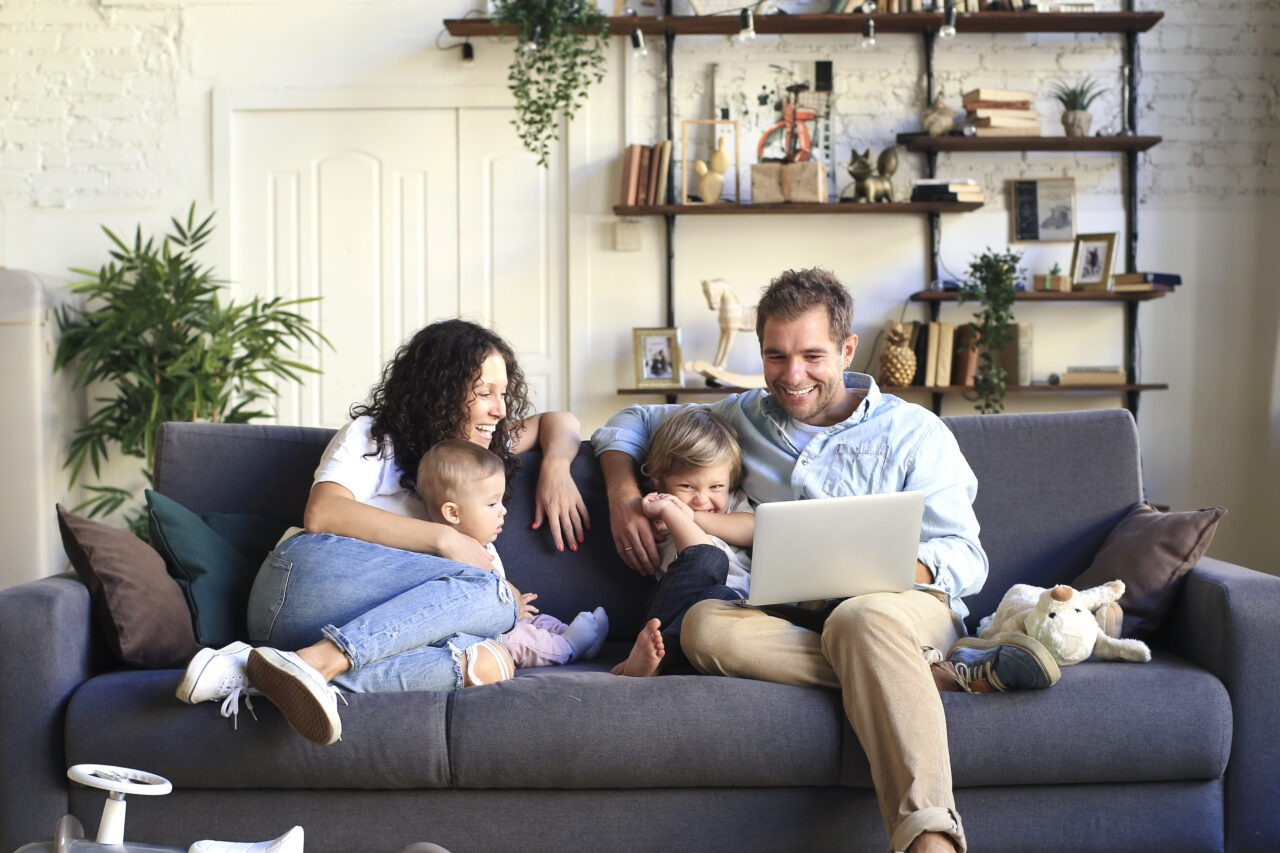 Family on couch looking at laptop